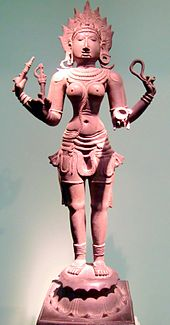 A reddish bronze statue of a four-armed topless woman wearing a short pant sari, standing on a pedestal. She wears a flaming crown and various ornaments, she carries in her hands a goad, a noose, a bowl and a small broken trident.