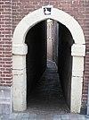 Hardstenen poortomlijsting, toegang tot het Vuilstraatje. Een gans op de gebeeldhouwde sluitsteen