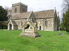 Gray stone building with small square tower at left hand end. In the foreground is grass with a small tiled memorial.