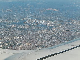 Adelaide Plains - Aerial view of the Adelaide metropolitan area viewed from above the northern suburbs at the bottom of the image. The city centre is the cluster of buildings in the centre, the Adelaide Hills are centre-right, the eastern suburbs on the far left and the southern suburbs far centre.