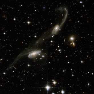 Triangulum Australe - ESO 69-6, two merging galaxies with prominent long tails, photographed by the Hubble Space Telescope