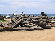 An unorganized pile of approximately 50 rosewood logs sits on a beach with boats in the background.