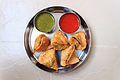 Indian snack called samosa served with sweet & sour ketchup and spicy chilly chutney.JPG