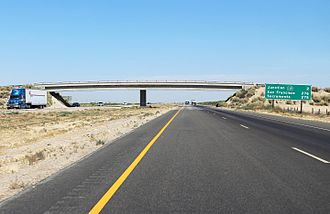 Interstate Highway System - A rural stretch of I-5 in California; two lanes in each direction are separated by a large grassy median and cross-traffic is limited to overpasses and underpasses