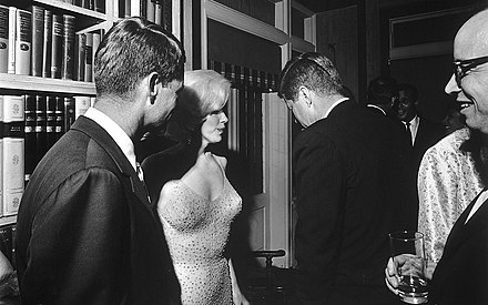 "Attorney General Robert F. Kennedy, Marilyn Monroe, and John Kennedy talk during the president's 19 May, 1962 early birthday party where Monroe publicly serenaded JFK with ""Happy Birthday, Mr. President"" JFK and Marilyn Monroe 1962.jpg"