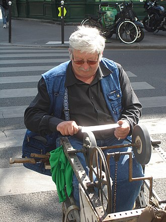 Sharpening - A roadside knife grinder on rue Faidherbe (11e arrondissement) in Paris. He is one of the few knife grinders who still practise in France.