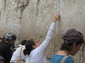 Placing notes in the Western Wall - A girl places a note into a crack of the Western Wall in Jerusalem.