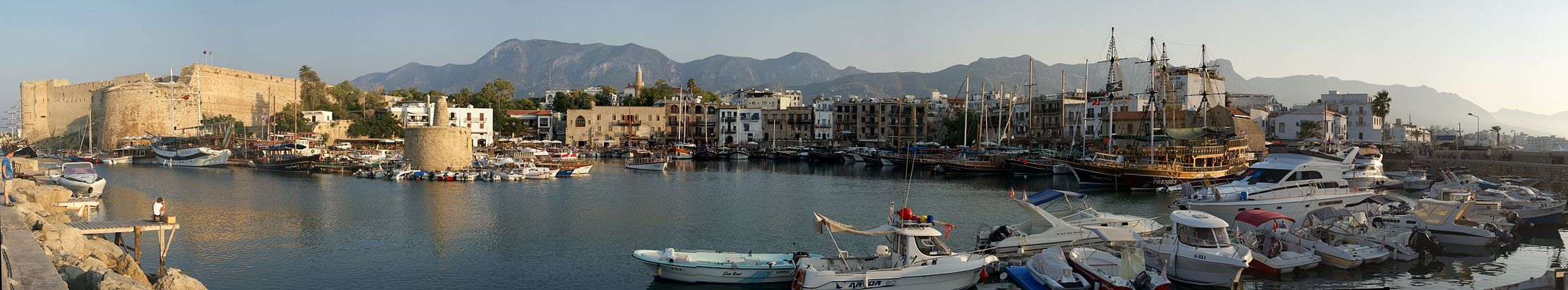 Panoramic view of the Kyrenia Harbour, with the Venetian era Kyrenia Castle on the far left, and the Kyrenia Mountains in the background.