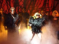 A group of people stand on a stage in black, feathery dresses and black sunglasses. Prominent among them is a blond woman, with a mouthpiece attached to her ear. Behind the group, a red background can be seen, interspersed with black thorn-like structures.