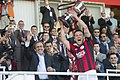 Lincoln Red Imps Captain Lifting 2014 Rock Cup from Michel Platini.jpg