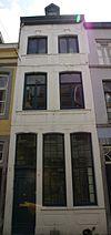 foto van Huis met lijstgevel, voorzien van vensters in segmentboogomlijstingen van Naamse steen en onderbroken verticale reliefbanden.