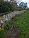 Tiles of children's artwork covering a low wall in Mallory Meadows Park