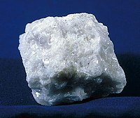 An irregularly shaped rock, milky-white in color. The rock glistens or sparkles from the overhead lights.