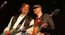 Mark Tulin--a middle-aged Caucasian male with long brown hair wearing a white shirt and black vest--plays bass guitar and smiles while Billy Corgan--a middle-aged Caucasian male wearing a dark green hat and red-and-black striped shirt with a brown jacket--plays electric guitar to his left.
