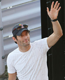 A man in his mid-thirties waving his left hand. He is wearing a white T-shirt and a dark blue hat with sunglasses on top