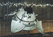 Zdjęcie. Model w muzeum. Okrągła kapsuła z rozłożonymi pokrywami i wystającymi antenami.