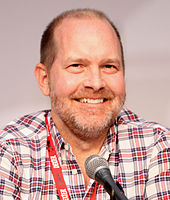 A man with closely shaven hair, and slight stubble, looking to the side slightly with his eyes, behind a microphone