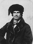 Black and white photograph of a man with a short moustache and earrings, wearing a fur lined dress jacket, bow tie and fur hat