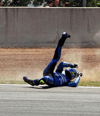 Motorcycle personal protective equipment - A motorcyclist wearing helmet, gloves, boots and leathers slides along a racetrack after crashing