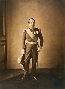 Photographie en sépia de Napoléon trois, de plain pied. Il porte un uniforme militaire et tient un bicorne de sa main droite. Son visage arbore un air éteint, comme sur de nombreuses photographies.