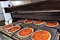 Nestlé-Wagner-Pizza wird mit Sauce vorgebacken.jpg