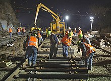 A crew of men in orange vests with reflector stripes and neon green hard hats over their clothing laying new railroad ties. Behind them is a large yellow piece of heavy equipment. It is night, and the scene is illuminated by large lights.