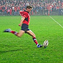 A man in a red shirt is running forward to kick a rugby ball placed on a tee.