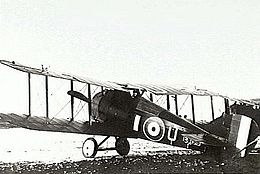 Rear three-quarter view of military biplane on landing ground