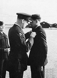 Three men in dark military uniforms; one pins a badge on another's chest