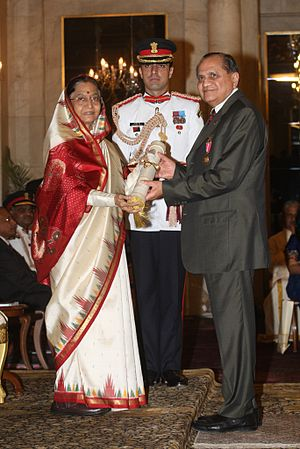 Photograph of Ramdas Pai receiving an award from then–President of India Padma Bhushan, a guard standing in the middle behind them both
