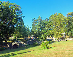 A grassy landscape with trees in the background. In front of them is a small creek with two stone bridges. A tall monument is at right