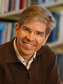 Romer smiling, seated in front of a bookshelf