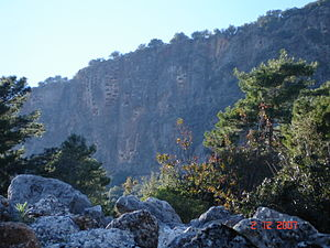 """Pinara - Crag with rock-cut tombs towering over Pinara situated on a """"round"""" mass of rock, believed to have given the ancient city its name."""