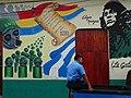 Policeman with Revolutionary Mural - Leon - Nicaragua (31416425952).jpg