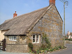 Old stone building with thatched roof on road junction.