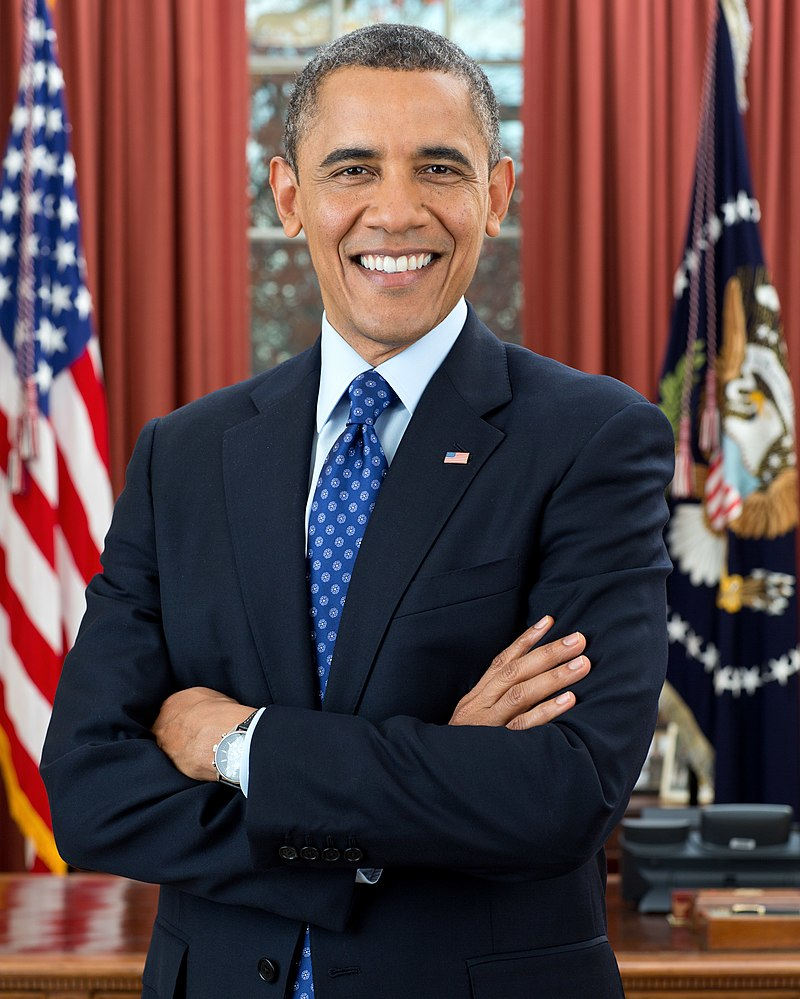 Obama standing with his arms folded and smiling