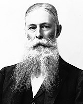 portrait shot of a man of about sixty, with hair combed across his head and with a beard divided in two. He wears a suit coat but his neckwear is obscured by the beard.