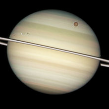 Zoom sur Saturne, on observe trois petits points blancs et un point orange beaucoup plus gros (Titan) au premier plan.