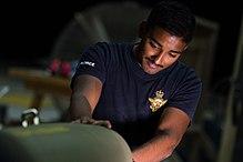 Ein Mann, der ein blaues T-Shirt mit einem militarischen Logo tragt, das an einer grunen Bombe arbeitet