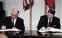La photographie couleur montre les deux chefs d'état attablés pour une signature conjointe. Derrière eux, les drapeaux américain et soviétique ornent le mur.