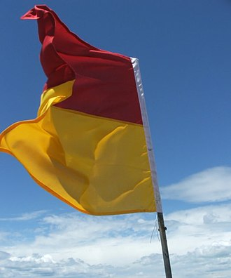 Lifeguard - Red and yellow flag indicating a bathing area patrolled by lifeguards.