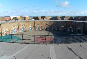 Eastbourne Redoubt - View across the redoubt from the rampart, showing the circular parade ground, the doors and windows of the casemates and the terreplein or gun platform above them.