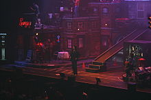 A man standing in front of the audience while in the middle of a concert, surrounded by the apartment-styled scenography and the rest of the musicians.