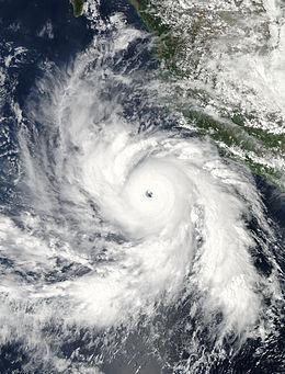 Immagine satellitare visibile di un potente uragano maturo vicino alla costa occidentale del Messico.  La tempesta presenta un occhio chiaro e ben definito circondato da una grande massa di intensa convezione.  Bande di alimentazione rotanti, curvate nel sistema, sono presenti intorno all'intero uragano.