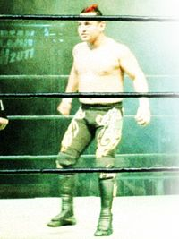 A color photo of a Mexican male wearing long black tights, standing in a wrestling ring