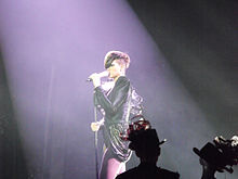 Photograph of a woman who sings on stage. She wears a dark leather blouse and a short skirt, and light tights.