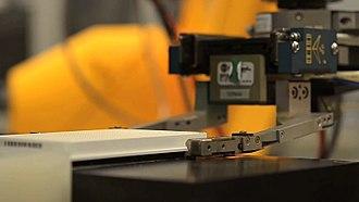 High-throughput screening - A robot arm handles an assay plate