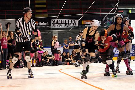 A German pivot attempts to knock a Dutch jammer out of bounds (the yellow line) at a 2011 bout held in Essen, Germany. Roller derby, Amsterdam Derby Dames against the Ruhr Pott Roller Girls from Essen, Germany.jpg