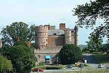 A large brick building built in the style of a medieval castle; grass, bushes and some trees in the foreground.