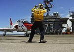 Sailor directs a T-45C Goshawk on the flight deck of the USS George Washington. (26609785784).jpg